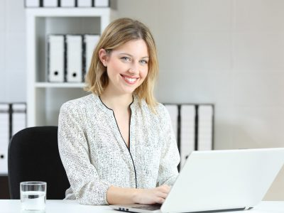 Portrait of a happy office employee working with a laptop and looking at camera